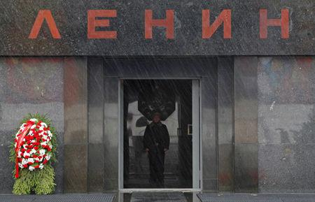 "FILE PHOTO: An honour guard is seen though the rain drops during a wreath-laying ceremony, held by supporters of the Russian Communist Party, at Vladimir Lenin's mausoleum on the eve of the 95th anniversary of the 1917 Bolshevik revolution in Red Square in Moscow, November 6, 2012. The sign reads ""Lenin"". REUTERS/Maxim Shemetov/File Photo"