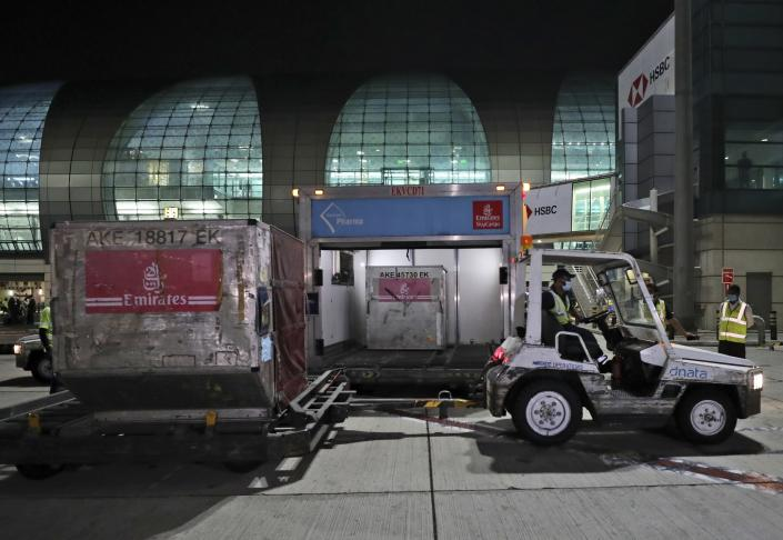 A shipment of Pfizer-BioNTech coronavirus vaccines is offloaded from an Emirates Airlines Boing 777 that arrived from Brussels to Dubai International Airport in Dubai, United Arab Emirates, Saturday, Feb. 20, 2021. As the coronavirus pandemic continues to clobber the aviation industry, Emirates Airlines, the Middle East's biggest airline, is seeking to play a vital role in the global vaccine delivery effort. (AP Photo/Kamran Jebreili)