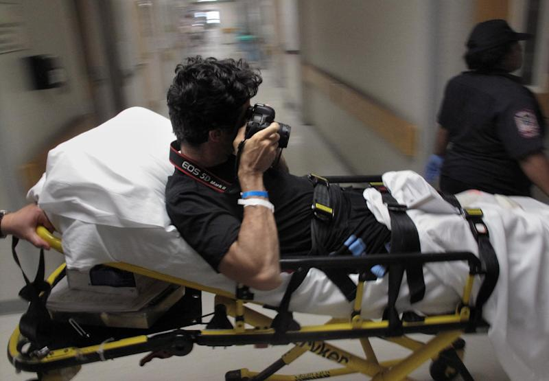 In this Aug. 25, 2009 picture, photographer Emilio Morenatti takes pictures as he is carried on a stretcher at University of Maryland Medical Center's R. Adams Cowley Shock Trauma Center in Baltimore, Md. For those who lost a limb or more in the Boston Marathon, Monday, April 15, 2013, was the day their world changed forever. Emilio's world changed also, on Tuesday, Aug. 11, 2009, when during his embed in southern Afghanistan with the U.S. military as a photographer for The Associated Press, which was to have been his last patrol before going home, the eight-wheel armored Stryker vehicle where he was traveling in with U.S soldiers hit a roadside bomb and flipped over, knocking him unconscious. Morenatti lost his leg in the bomb blast. (AP Photo/Enric Marti)