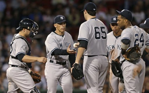 New York Yankees starting pitcher Phil Hughes hands the ball to manager Joe Girardi in the eighth inning of a baseball game against the Boston Red Sox, Thursday, Sept. 13, 2012, at Fenway Park in Boston. Hughes allowed no runs and five hits, and struck out seven. (AP Photo/Charles Krupa)