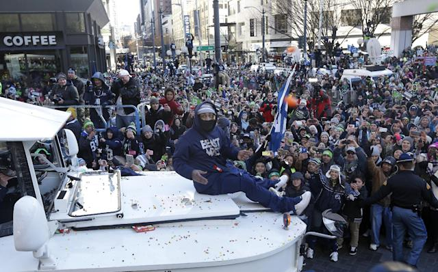 Seattle Seahawks' running back Marshawn Lynch throws pieces of candy while riding on the hood of a vehicle during the Super Bowl champions parade, Wednesday, Feb. 5, 2014, in Seattle. The Seahawks defeated the Denver Broncos 43-8 in NFL football's Super Bowl XLVIII on Sunday. (AP Photo/Ted S. Warren)