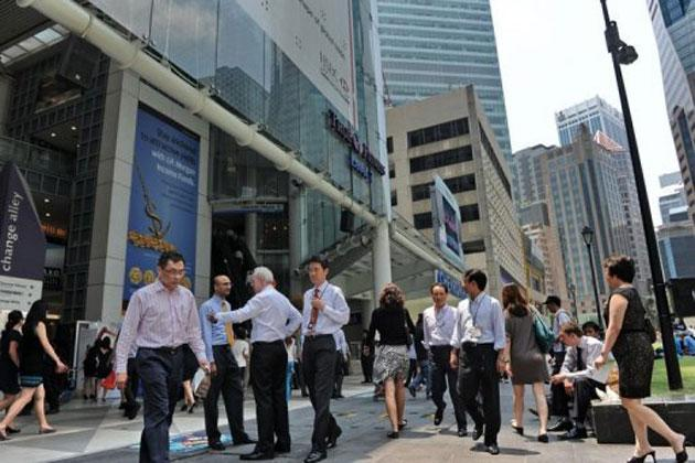 People walk through Raffles Place in Singapore on October 1, 2012. (AFP photo)