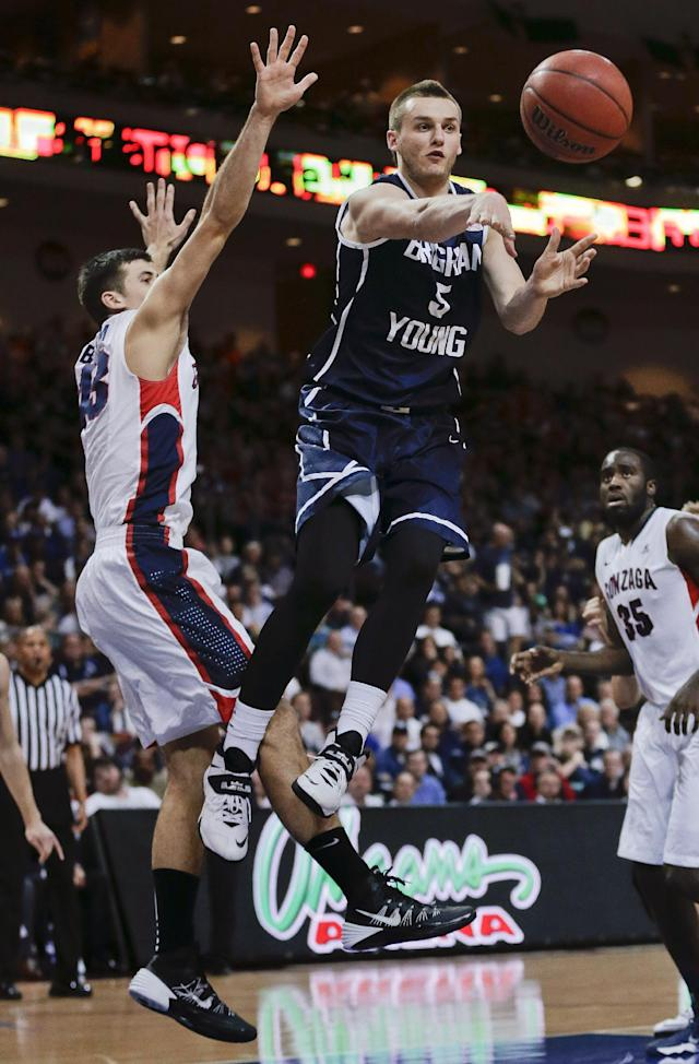 BYU's Kyle Collinsworth (5) passes off the ball against Gonzaga's Drew Barham, left, during the second half of an NCAA college basketball game for the West Coast Conference men's tournament title, March 11, 2014, in Las Vegas. Gonzaga won 75-64. (AP Photo/Julie Jacobson)