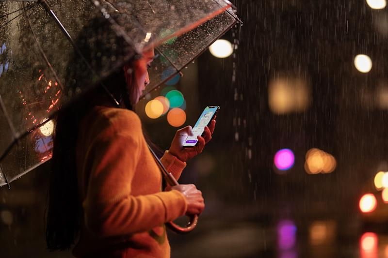 A woman uses an iPhone XS Max in the rain.
