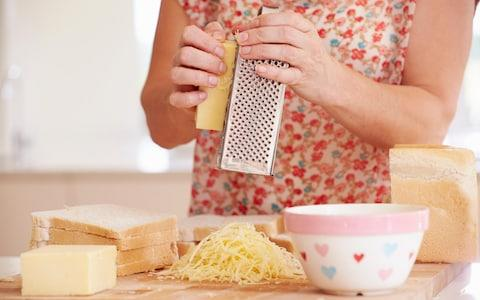 Close up of woman grating cheese in her kitchen - Credit:  MBI / Alamy Stock Photo