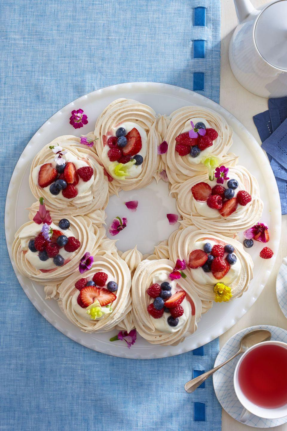 """<p>This recipe calls for edible flowers, but you can switch them out and add more strawberries!</p><p><em><a href=""""https://www.womansday.com/food-recipes/food-drinks/recipes/a58133/meringue-wreath-recipe/"""" rel=""""nofollow noopener"""" target=""""_blank"""" data-ylk=""""slk:Get the recipe for Meringue Wreath."""" class=""""link rapid-noclick-resp"""">Get the recipe for Meringue Wreath.</a></em></p>"""