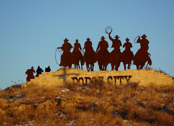 A steel cutout of cowboys riding toward the sunset welcomes visitors to Dodge City, Kan.