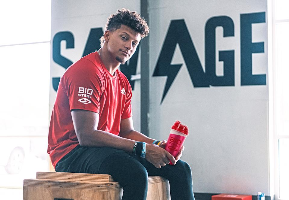 Patrick Mahomes wears a red BioSteel shirt and holds a red BioSteel cup.
