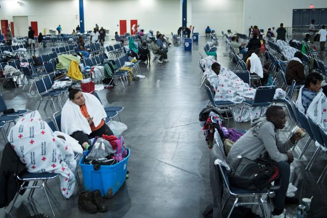 <p>Flood victims rest at a shelter in the George R. Brown Convention Center during the aftermath of Hurricane Harvey on Aug. 28, 2017 in Houston, Texas. (Photo: Brendan Smialowski/AFP/Getty Images) </p>