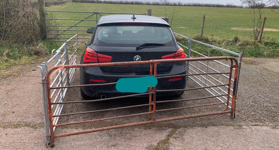 A BMW is pictured parked in front of a farm gate with a temporary fence built around it.