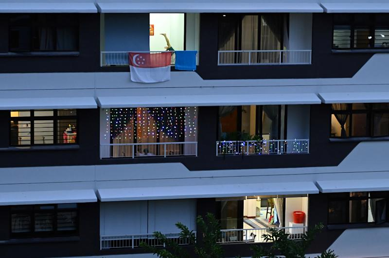 A Singapore flag is seen on the balcony of a flat in Singapore on 23 May, 2020. (PHOTO: AFP via Getty Images)
