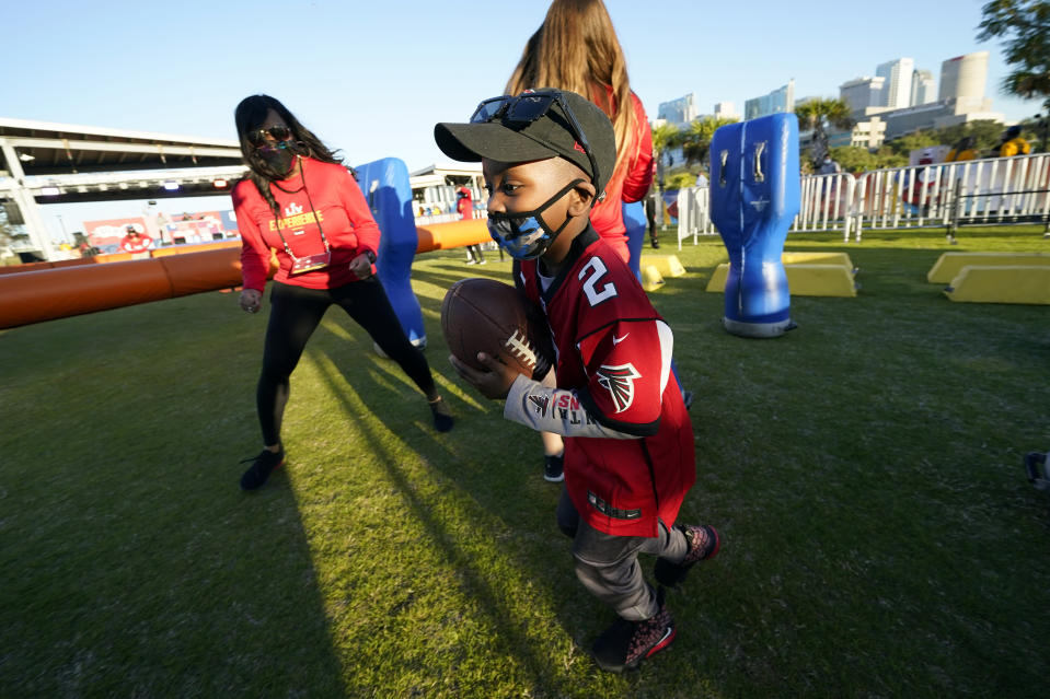 Isaiah Sheppard, 7, runs with a football at the NFL Experience for Super Bowl LV Friday, Jan. 29, 2021, in Tampa, Fla. (AP Photo/David J. Phillip)