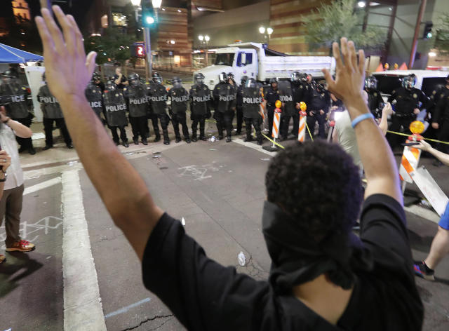 <p>Protesters raise their hands after Phoenix police used pepper spray outside the Phoenix Convention Center, Tuesday, Aug. 22, 2017, in Phoenix. Protests were held against President Trump as he hosted a rally inside the convention center. (AP Photo/Matt York) </p>