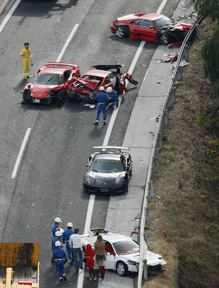 Police officers investigate damaged luxuary cars at the site of a traffic accident on the Chugoku Expressway in Shimonoseki, southwestern Japan, Sunday, Dec. 4, 2011. Thirteen sports cars, including eight Ferraris, a Lamborghini and two Mercedes-Benz, were involved in the accident, slightly injuring 10 people. (AP Photo/Kyodo News) JAPAN OUT, MANDATORY CREDIT, NO LICENSING IN CHINA, FRANCE, HONG KONG, JAPAN AND SOUTH KOREA