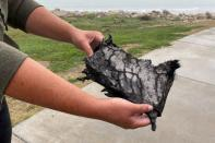 A spectator holds a piece of debris which was blown 5 miles from the site where SpaceX test rocket SN11 exploded upon landing, in Boca Chica