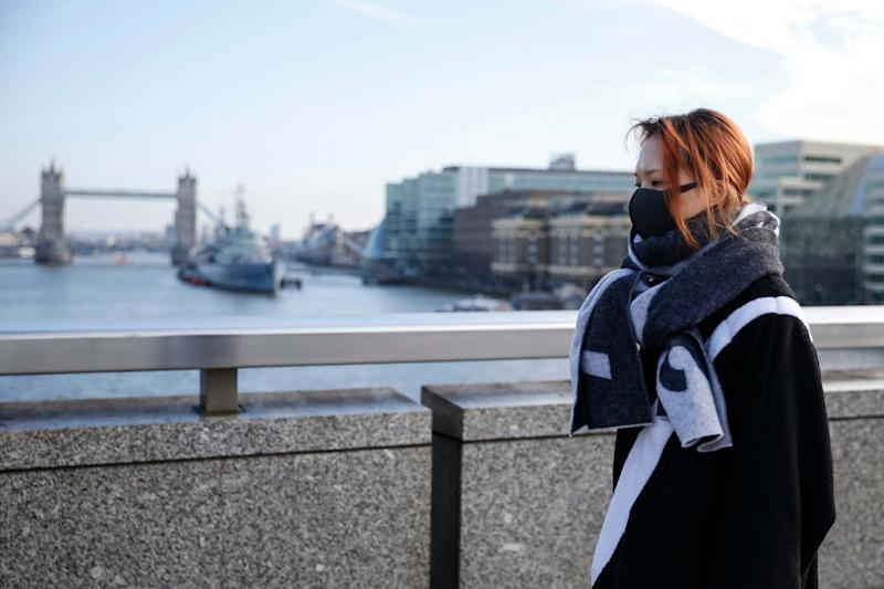 A woman wears a mask while crossing London Bridge (Getty Images)