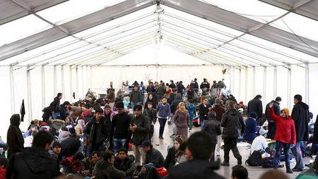 Migrants wait in a tent before passing through the Austrian-German border from Austria