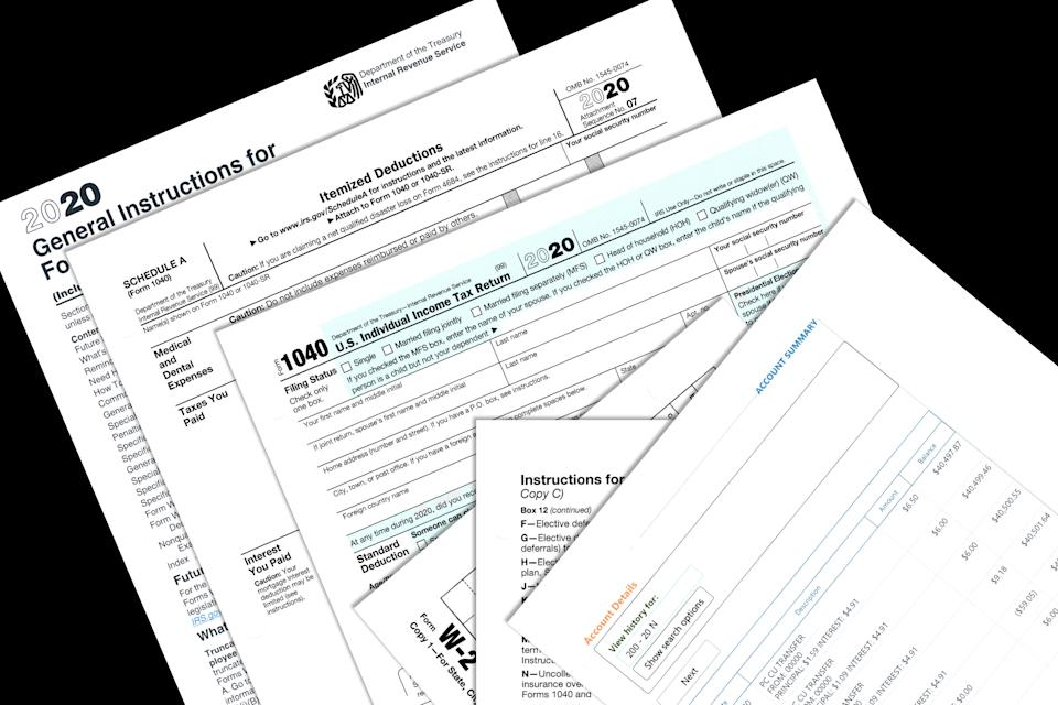 2020 IRS tax forms and imitation personal papers on a desktop.
