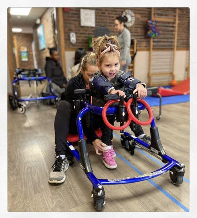 a girl with a disability in therapy working on walking.