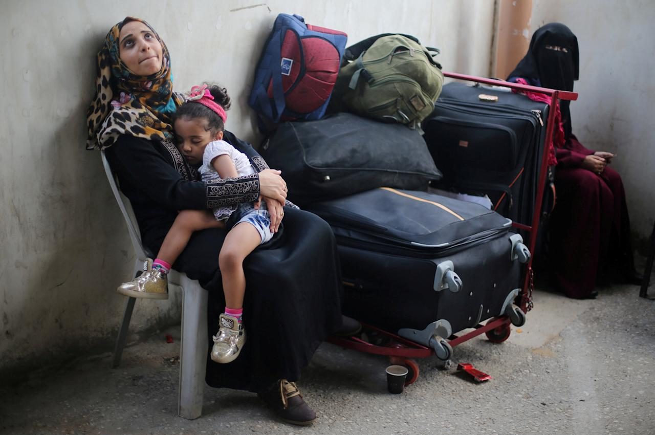 A Palestinian woman holds her daughter as they wait for a travel permit to cross into Egypt through the Rafah border crossing after it was opened by Egyptian authorities for humanitarian cases, in Rafah in the southern Gaza Strip August 16, 2017. REUTERS/Ibraheem Abu Mustafa     TPX IMAGES OF THE DAY