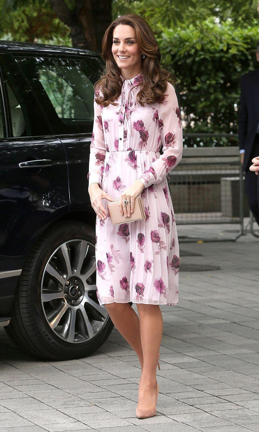 <p>Middleton wears a light pink chiffon Kate Spade dress with a rose pattern, a tie neck and pleated skirt, paired with a nude clutch and suede heeled pumps at while celebrating at World Mental Health Day in London. </p>