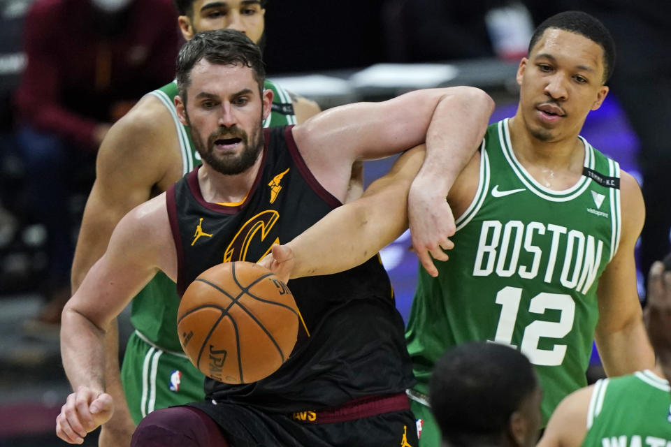 Cleveland Cavaliers' Kevin Love, left, and Boston Celtics' Grant Williams vie for the ball during the second half of an NBA basketball game Wednesday, May 12, 2021, in Cleveland. The Cavaliers won 102-94. (AP Photo/Tony Dejak)