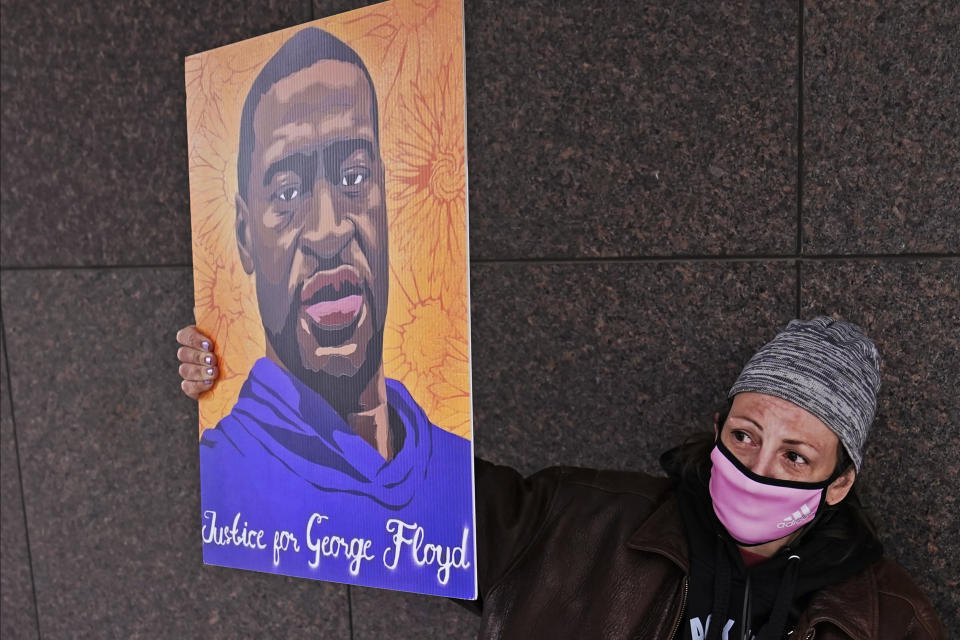 A woman holds up a George Floyd poster across from the Hennepin County Government Center, Tuesday, April 20, 2021, in Minneapolis, after jurors found former Minneapolis police officer Derek Chauvin guilty on all counts of murder and manslaughter in the death of Floyd. (AP Photo/Jim Mone)