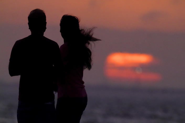 FILE - In this Feb. 6, 2021, file photo, people watch the sun set over Tampa Bay in Tampa, Fla. Amid fears of new variants of the virus, new restrictions on movement have hit just as people start to look ahead to what is usually a busy time of year for travel. (AP Photo/Charlie Riedel, File)