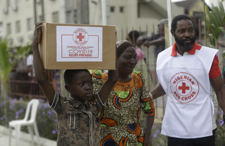 A child with his mother from Makoko Slum, carries their food parcel distributed by the Nigerian Red Cross, provided for those under coronavirus related movement restrictions, in Lagos, Nigeria, Saturday, April 25, 2020. (AP Photo/Sunday Alamba)