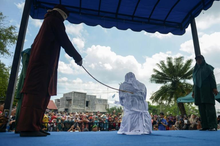 More than a thousand people, including dozens of tourists from neighbouring Malaysia, jeered and screamed abuse at the group as they were flogged outside a mosque in the capital Banda Aceh