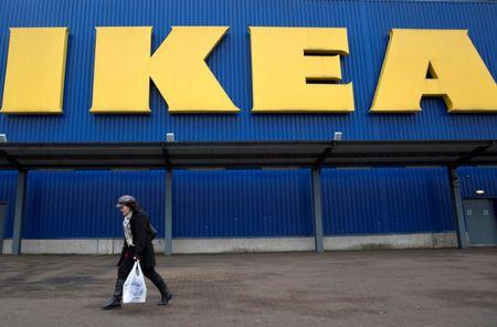 FILE PHOTO: A shopper walks past a sign outside an IKEA store in Wembley, north London