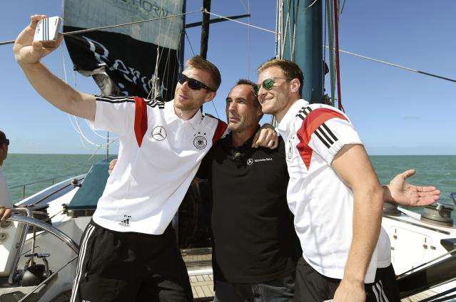 Germany's national soccer team players Per Mertesacker (L) and Benedikt Hoewedes (R) take a picture together with explorer and adventurer Mike Horn of Switzerland (C) aboard the sailing ship 'Pangaea' near Santo Andre village, near Porto Seguro June 10, 2014. REUTERS/Markus Gilliar/Pool (BRAZIL - Tags: SPORT SOCCER WORLD CUP )