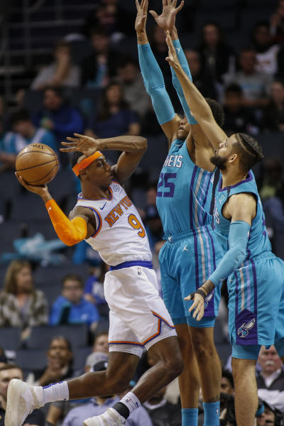 New York Knicks guard RJ Barrett, left, tries to pass the ball around Charlotte Hornets forwards P.J. Washington and Cody Martin, right, during the first half of an NBA basketball game in Charlotte, N.C., Wednesday, Feb. 26, 2020. (AP Photo/Nell Redmond)