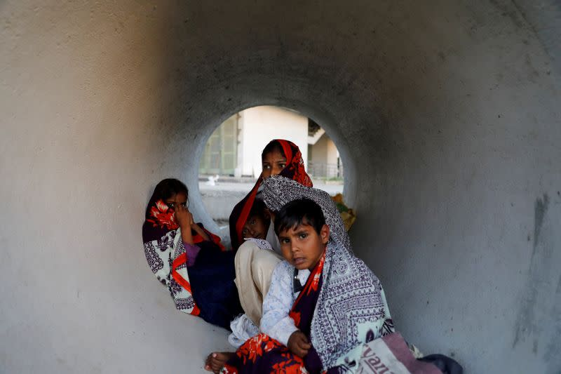 Family of a migrant worker shelters in a pipe kept along a highway as they wait to board their bus to return to their village, during a 21-day nationwide lockdown to limit the spreading of coronavirus disease (COVID-19), in Ghaziabad