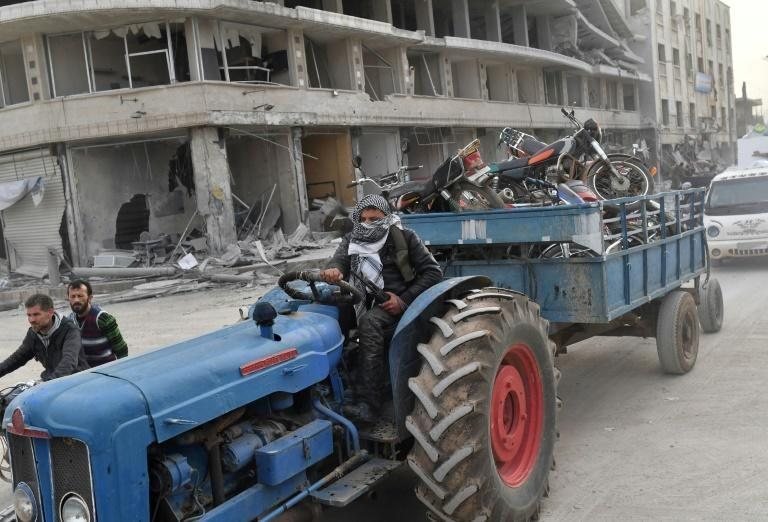 A Turkish-backed Syrian Arab fighter tows towing looted items in a trailer after seizing control of the northwestern Syrian city of Afrin from the Kurdish People's Protection Units (YPG) on March 18, 2018