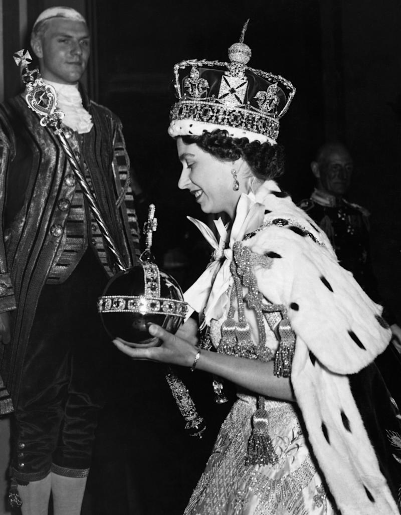 Queen Elizabeth II, wearing the Imperial State Crown and carrying the Orb, arrives at Buckingham Palace from Westminster Abbey, after her coronation in 1953. (Photo by © Hulton-Deutsch Collection/CORBIS/Corbis via Getty Images)
