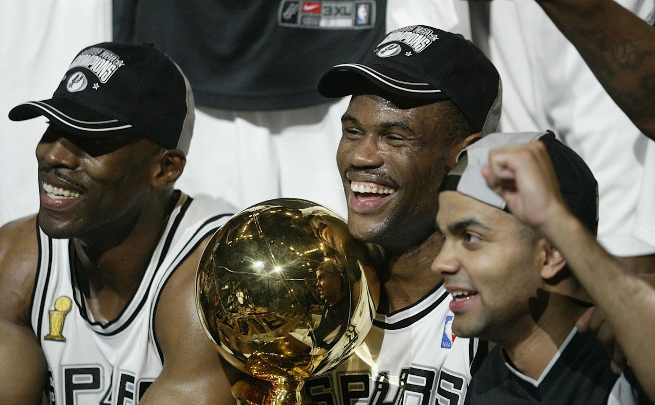 SAN ANTONIO - JUNE 15:  David Robinson #50, Kevin Willis #42 and Tony Parker #9 of the San Antonio Spurs celebrate with the championship trophy after defeating the New Jersey Nets 88-77 during game six of the 2003 NBA Finals on June 15, 2003 at the SBC Center in San Antonio, Texas.  NOTE TO USER: User expressly acknowledges and agrees that, by downloading and/or using this Photograph, User is consenting to the terms and conditions of the Getty Images License Agreement.  (Photo by Jed Jacobsohn/Getty Images)