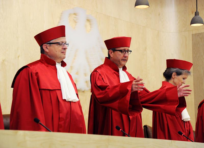 The Second Senate of the German Constitutional Court, from left: Peter Huber, chairman Andreas Vosskuhle and Gertrude Luebbe-Wolff, open a session at the German Constitutional Court in Karlsruhe, Germany, Wednesday June 12, 2013. A top European Central Bank official has defended the bank's key crisis backstop in a second day of hearings before Germany's Federal Constitutional Court. Joerg Asmussen told the eight judges that the ECB's plan to purchase government bonds was only aimed at making sure the bank's monetary policy is effective, not at rescuing governments in the 17-country eurozone. The ECB is prohibited by treaty from financing governments. But Asmussen insisted Wednesday that the ECB had not exceeded its powers with the bond purchases program, even to spare a country from going bankrupt. (AP Photo/dpa, Uli Deck)