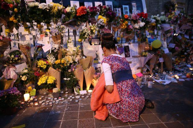 People look at tributes at Notting Hill Methodist Church near Grenfell Tower (Isabel Infantes/PA)