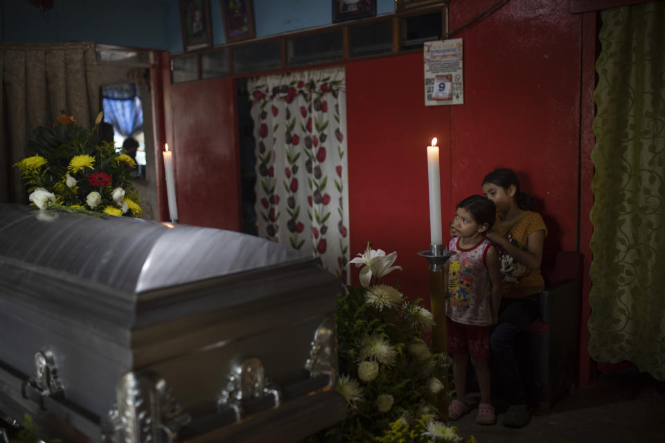 Two of six children of slain journalist Julio Valdivia stand by his casket during a wake inside their home in Tezonapa, Veracruz, Mexico, Thursday, Sept. 10, 2020. Valdivia's decapitated body was found five miles from Tezonapa a day earlier and is at least the third reporter killed in the area since 2015. (AP Photo/Felix Marquez)