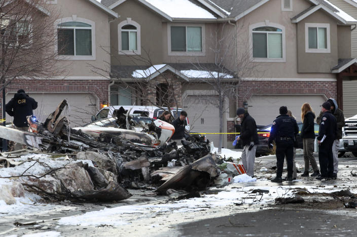 Emergency crews look through the debris from a small plane that crashed in a Roy, Utah, residential neighborhood, narrowly missing townhouses in the area, on Wednesday, Jan. 15, 2020. Roy police Sgt. Matthew Gwynn said the 64-year-old pilot was making a short flight from Bountiful to Ogden in a twin-engine Cessna Wednesday but crashed in the city of Roy about 30 miles north of Salt Lake City. (Steve Griffin/The Deseret News via AP)