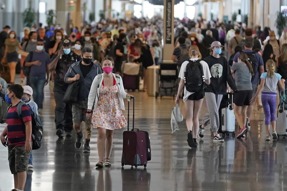 FILE - In this July 1, 2021, file photo, people walk through Salt Lake City International Airport in Salt Lake City. Americans enjoying newfound liberty are expected to travel and gather for cookouts, fireworks and family reunions over the Fourth of July weekend in numbers not seen since pre-pandemic days. (AP Photo/Rick Bowmer, File)