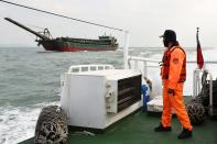Taiwanese coast guard looks at a sand-dredging ship with Chinese flag in the waters off the Taiwan-controlled Matsu islands