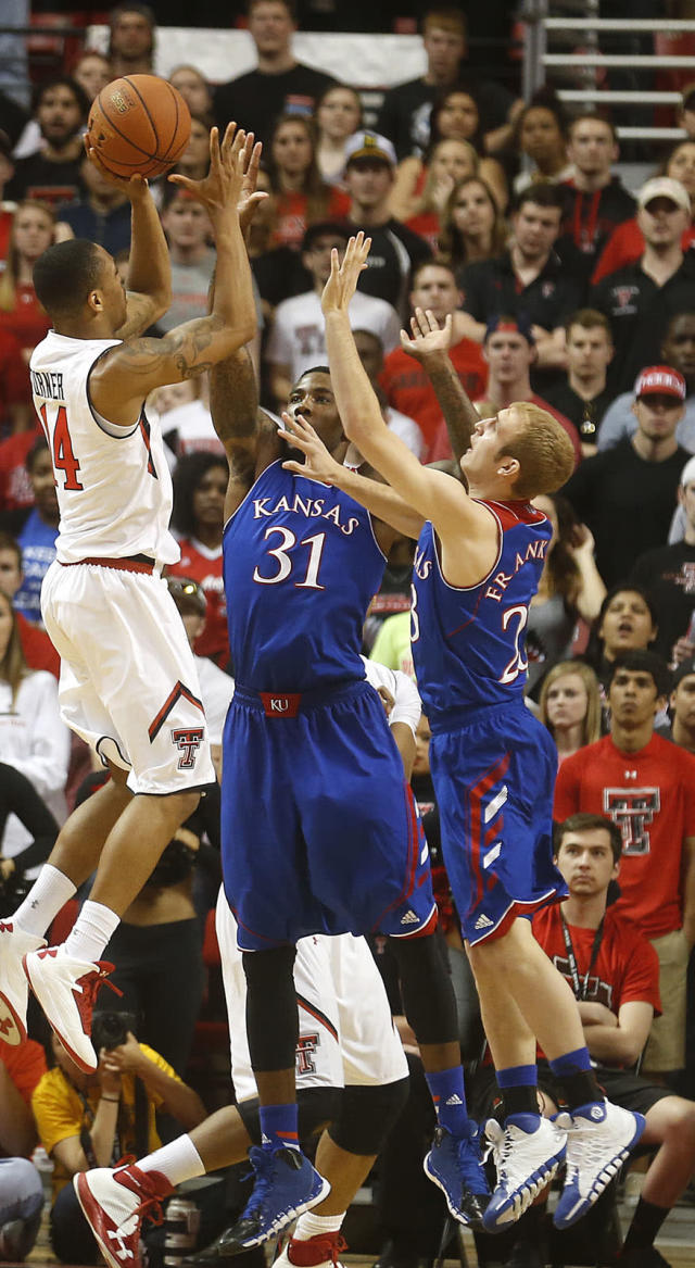 Texas Tech's Robert Turner (14) is defended by Kansas' Jamari Traylor (31) and Conner Frankamp (23) during their NCAA college basketball game in Lubbock, Texas, Tuesday, Feb, 18, 2014. (AP Photo/Lubbock Avalanche-Journal, Stephen Spillman)