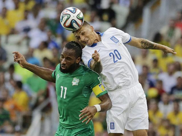Greece's Jose Holebas heads the ball over Ivory Coast's Didier Drogba during the group C World Cup soccer match between Greece and Ivory Coast at the Arena Castelao in Fortaleza, Brazil, Tuesday, June 24, 2014. (AP Photo/Bernat Armangue)