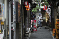 A man wearing a protective mask to help curb the spread of the coronavirus walks along an empty bar street Tuesday, June 22, 2021, in Tokyo. The Japanese capital confirmed more than 430 new coronavirus cases on Tuesday. (AP Photo/Eugene Hoshiko)