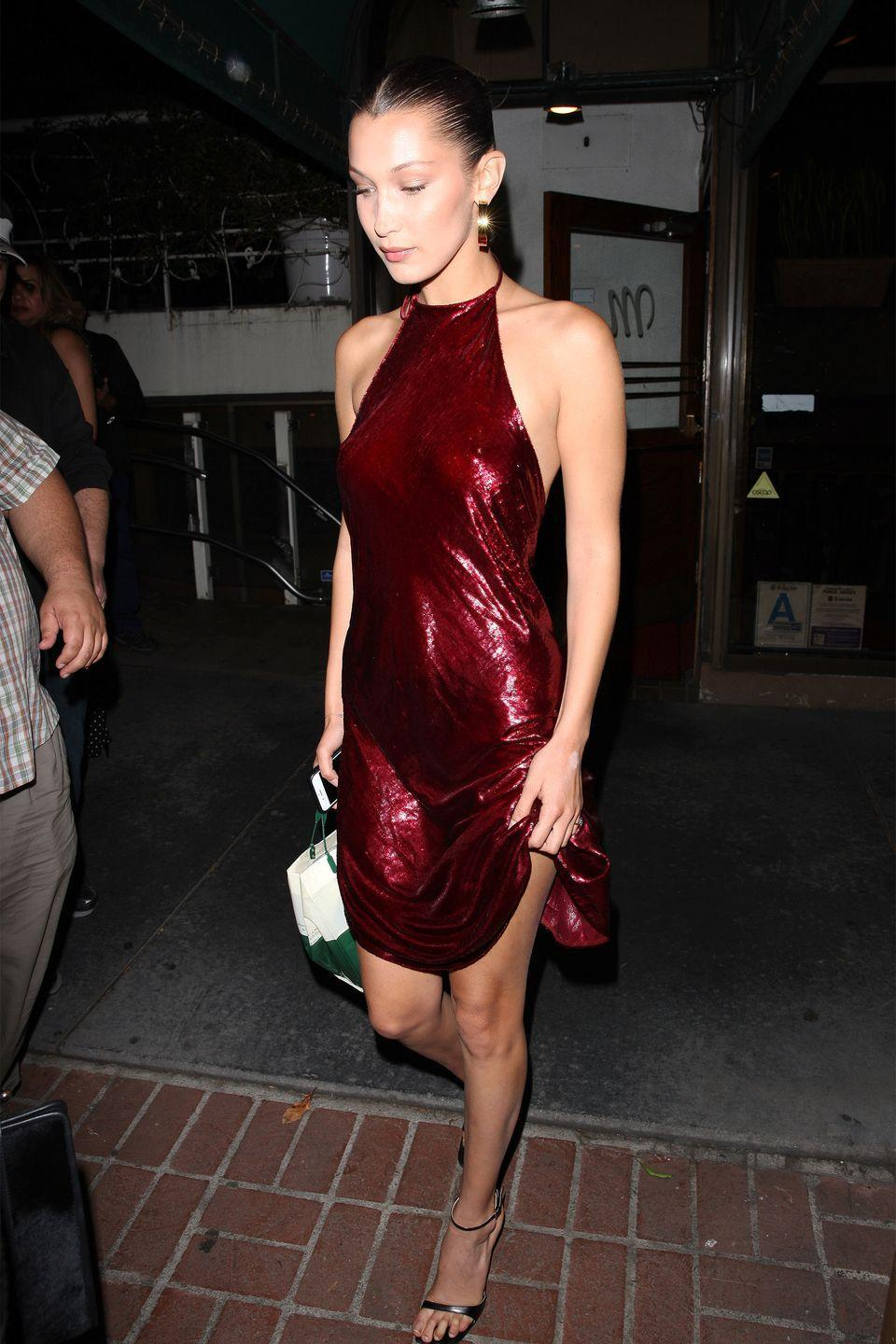 <p>In a shimmery Area velvet red halter dress, gold hoop earrings and metallic sandals while out to dinner in West Hollywood for Father's Day.</p>