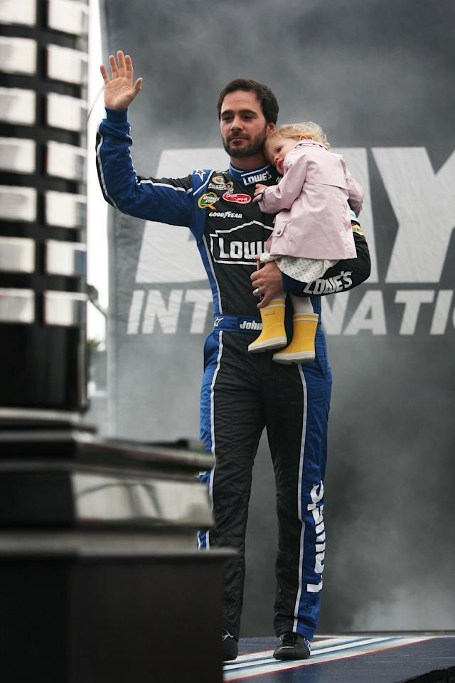DAYTONA BEACH, FL - FEBRUARY 26: Jimmie Johnson, driver of the #48 Lowe's Chevrolet, waves to fans while holding daughter Genevieve Marie during driver introductions prior to the start of the NASCAR Sprint Cup Series Daytona 500 at Daytona International Speedway on February 26, 2012 in Daytona Beach, Florida. (Photo by Jerry Markland/Getty Images for NASCAR)