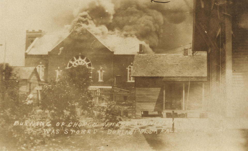 In this photo provided by the Department of Special Collections, McFarlin Library, The University of Tulsa, the Mt. Zion Baptist Church burns during the Tulsa Race Massacre in Tulsa, Okla., on June 1, 1921. (Department of Special Collections, McFarlin Library, The University of Tulsa via AP)