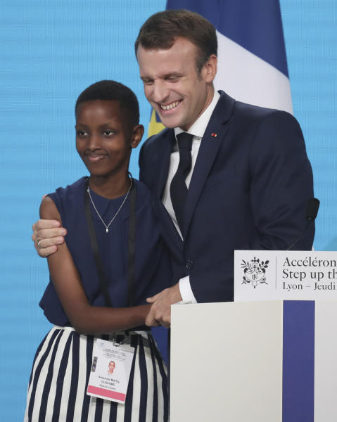 "France's President Emmanuel Macron, right, poses with goodwill ambassador of the ONG ""Grandir Ensemble"" Amanda Dushime at the Lyon's congress hall, central France, Thursday, Oct. 10, 2019, during the meeting of international lawmakers, health leaders and people affected by HIV, Tuberculosis and malaria. Lyon is hosting the two day Global Fund event aimed at raising money to help in the global fight against the epidemics. (AP Photo/Laurent Cipriani)"